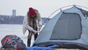 一个红色帽子的可爱的年轻旅游妇女在海岸的森林附近收集旅游帐篷 免版税库存图片