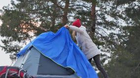 一个红色帽子的可爱的年轻旅游妇女在海岸的森林附近收集旅游帐篷 库存图片