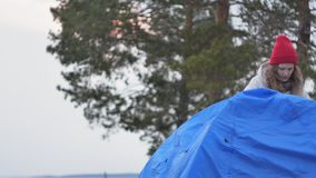 一个红色帽子的可爱的年轻旅游妇女在海岸的森林附近收集旅游帐篷 库存照片