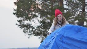 一个红色帽子的可爱的年轻旅游妇女在海岸的森林附近收集旅游帐篷 免版税库存照片