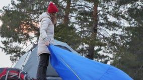 一个红色帽子的可爱的年轻旅游妇女在海岸的森林附近收集旅游帐篷 图库摄影