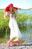 一个红色帽子的女孩和一个轻的夏天穿戴 库存图片