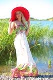 一个红色帽子的女孩和一个轻的夏天穿戴 库存照片