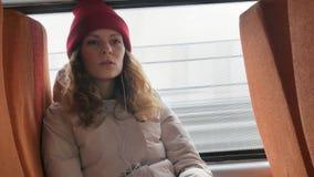 一个红色帽子的年轻快乐的妇女,旅行乘公共汽车在一哀伤的天 听到音乐的她 股票视频