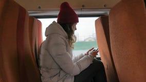 一个红色帽子的年轻快乐的妇女,旅行乘公共汽车在一哀伤的天 听到音乐的她 影视素材