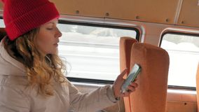 一个红色帽子的年轻快乐的妇女,旅行乘公共汽车在一哀伤的天 听到音乐的她 股票录像