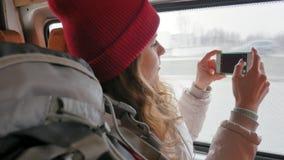 一个红色帽子的年轻快乐的妇女,旅行乘公共汽车在一哀伤的天 她拍在智能手机的照片 股票录像