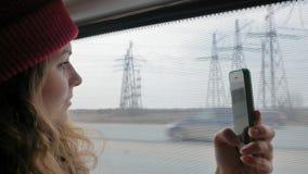一个红色帽子的年轻快乐的妇女,旅行乘公共汽车在一哀伤的天 她拍在智能手机的照片 影视素材