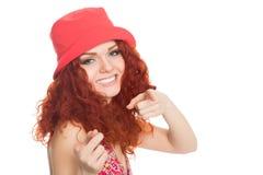 一个红色帽子的快乐的女孩指向照相机的 库存图片