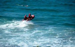 一个红色救助艇的海滩别动队员附近游泳的冲浪者 免版税库存图片