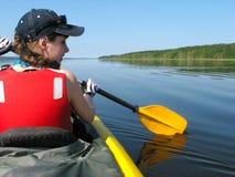 一个红色救生衣行的女孩在一个湖的一艘皮船晴朗的s的 免版税库存照片