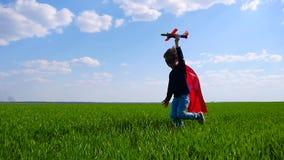 一个红色斗篷和面具奔跑的一个孩子,在他的手上拿着一架飞机,代表飞行 股票视频