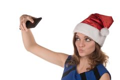 一个红色新年帽子的女孩有在背景的一个手机的 库存图片