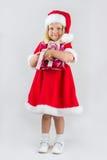 一个红色新年盖帽的女孩 免版税库存照片