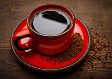 一个红色杯子鲜美速溶咖啡,木表面上 免版税库存照片