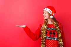 一个红色毛线衣和圣诞老人帽子的女孩,有闪亮金属片的在她的脖子上指向在红色背景的空的空间的 免版税库存照片