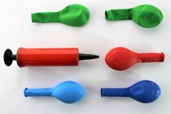 一个红色气球泵浦的图象在五颜六色的放气的气球之间的,在灰色背景 免版税库存照片