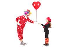 给一个红色气球的男性小丑一个小女孩 库存照片