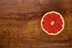 一个红色水多的切片在木桌上的葡萄柚 免版税库存照片