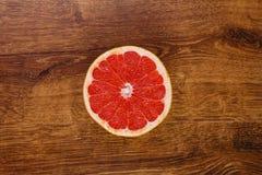 一个红色水多的切片在木桌上的葡萄柚 库存图片