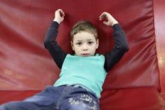 一个红色沙发的孩子 图库摄影