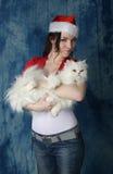 一个红色盖帽和一件夹克的女孩有一只白色蓬松猫的 库存图片