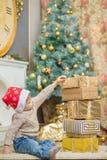 一个红色盖帽的一个男孩在与礼物的一棵圣诞树附近坐 免版税库存照片