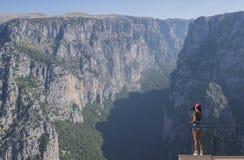 一个红色盖帽的一位女孩摄影师有照相机的在Vikos对面峡谷的阳台站立在希腊 Vikos峡谷在希腊 图库摄影