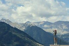 一个红色盖帽的一位女性摄影师有照相机的在希腊山对面的阳台和村庄站立在希腊 免版税图库摄影