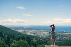 一个红色盖帽的一位女性摄影师有照相机的在希腊市的阳台对面站立卡泰里尼在日落 卡泰里尼 图库摄影