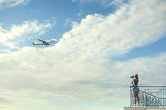一个红色盖帽的一位女性摄影师有照相机的在蓝天对面的阳台站立与云彩和飞机 妇女作为pict 库存图片