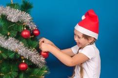 一个红色盖帽的女孩在与闪亮金属片的一根冷杉木挂上一个玩具a 免版税库存图片