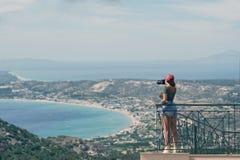 一个红色盖帽的女性摄影师有照相机的在希腊市的阳台对面站立沃洛斯在日落 沃洛斯希腊 免版税库存照片