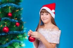 一个红色盖帽的小女孩在与闪亮金属片的一根冷杉木挂掉电话 库存图片