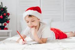 一个红色盖帽的男孩给圣诞老人写一封信 免版税库存照片