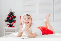 一个红色盖帽的男孩给圣诞老人写一封信 免版税库存图片