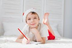 一个红色盖帽的男孩给圣诞老人写一封信 库存图片