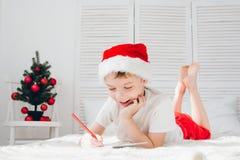 一个红色盖帽的男孩给圣诞老人写一封信 免版税图库摄影