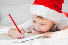 一个红色盖帽的男孩给圣诞老人写一封信 库存照片