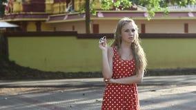 一个红色短上衣小点礼服身分的白肤金发的女孩摆在 股票录像