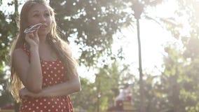 一个红色短上衣小点礼服身分的白肤金发的女孩摆在 影视素材