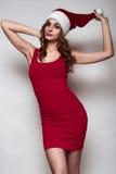 一个红色礼服和圣诞节帽子的典雅的美丽的妇女 库存图片