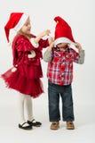 一个红色礼服和小男孩的女孩在圣诞老人帽子 免版税图库摄影