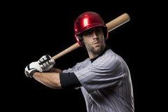 一个红色统一的棒球运动员。 库存图片