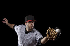 一个红色统一的棒球运动员。 免版税库存图片