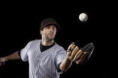 一个红色统一的棒球运动员。 图库摄影