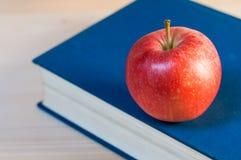 一个红色苹果和一本蓝皮书 图库摄影