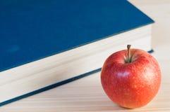 一个红色苹果和一本蓝皮书 库存图片