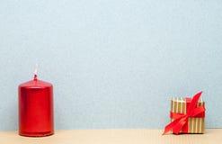 一个红色蜡烛和小礼物 免版税库存图片