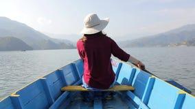 一个红色衬衣和帽子的女孩在有一支桨的一条木蓝色小船在她的从后面的手意图,在反对backgroun的湖 股票录像